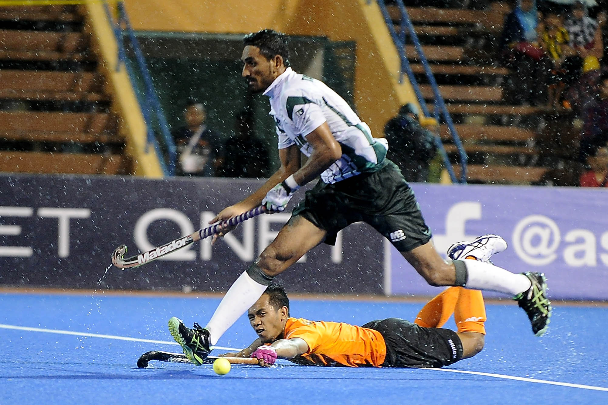 Malaysia's Faizal Saari (back) attempts to challenge a Pakistani player during their QNET 4th Men's Asian Champions Trophy 2016 semi-finals match at the Wisma Belia Hockey Stadium, Kuantan today. The full-time score was tied at 1-1 before Malaysia lost 3-2 in the shootout.