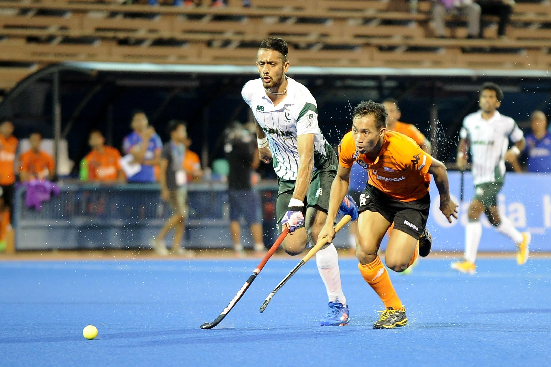 Nik Aiman Rosemi (right) races to the ball with a Pakistani defender caught on his heels during the opening match of the QNET 4th Men's Asian Champions Trophy 2016 at the Wisma Belia Hockey Stadium, Kuantan today. Malaysia won 4-2.