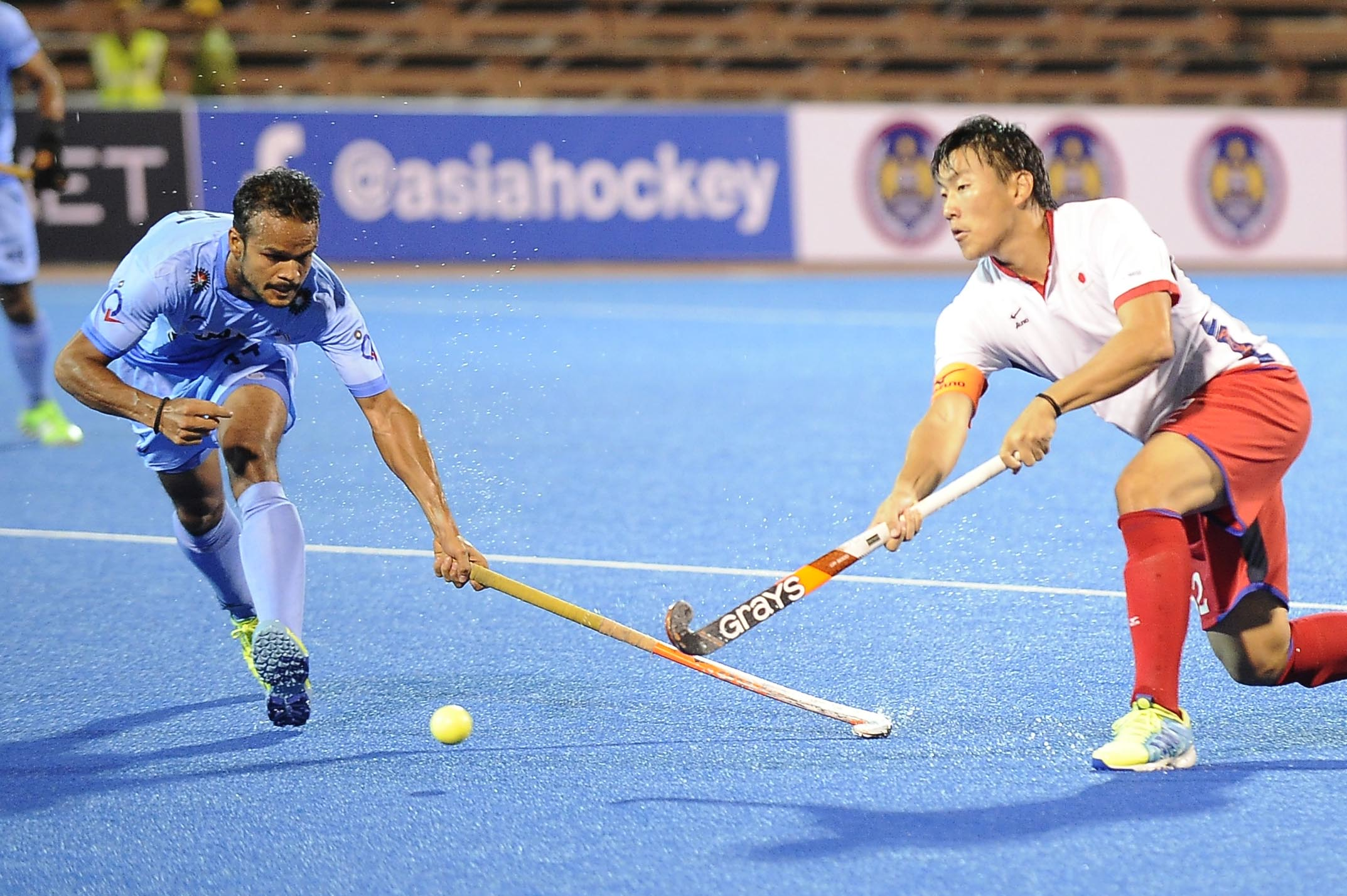 India's player (left) challenges a Japanese player for the ball during their QNET 4th Men's Asian Champions Trophy 2016 match at the Wisma Belia Hockey Stadium, Kuantan today. India won 10-2.