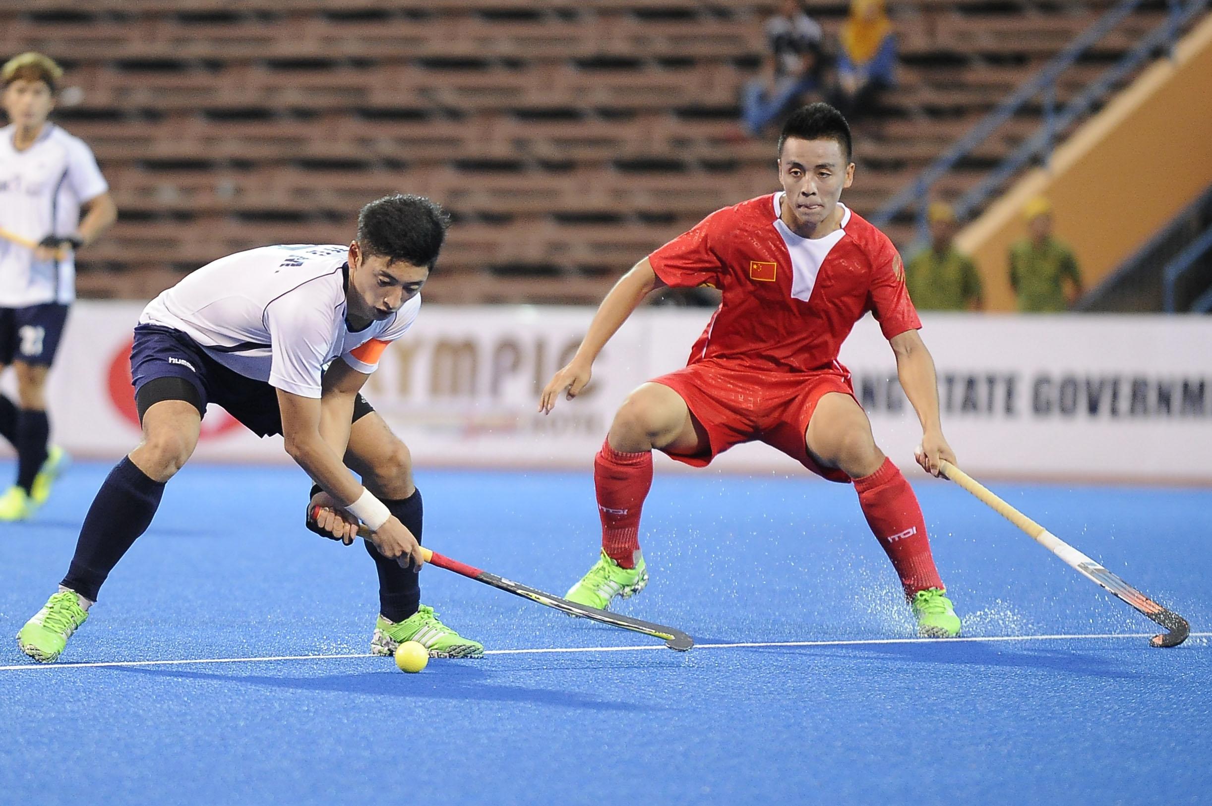 Ketua pasukan Korea, Jung Manjae (kiri) mengawal bola sambil cuba diasak oleh pemain China pada perlawanan QNET Trofi Juara-Juara Asia yang berlangsung di Stadium Hoki Wisma Belia, Kuantan sebentar tadi. Perlawanan berkesudahan Korea menang 5-3.