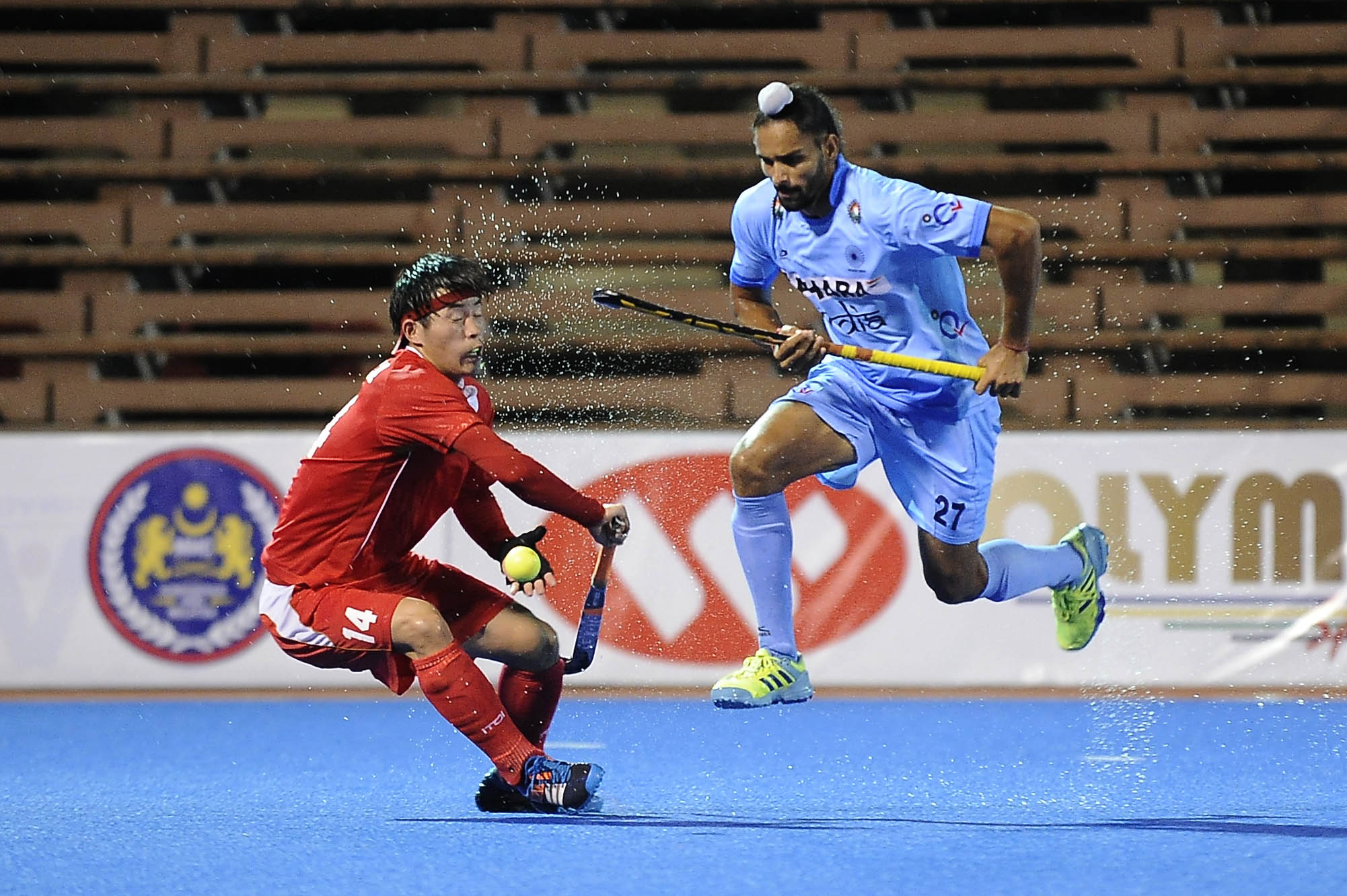 India's Akashdeep Singh (right) chips the ball past China's captain, Lei Meng just before registering India's first goal of the night in their QNET Asian Champions Trophy 2016 match at the Wisma Belia Hockey Stadium, Kuantan today. India won 9-0.